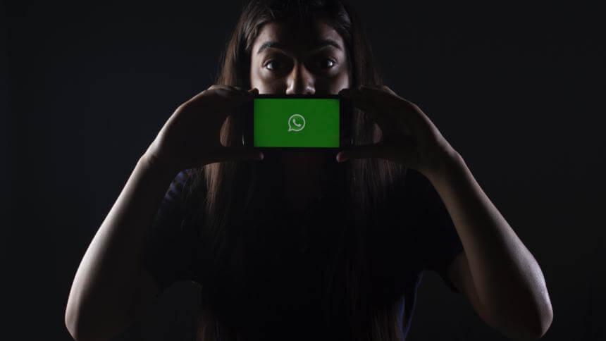 Frau mit Handy vor dem Mund, auf den das WhatsApp-Logo zu sehen ist.